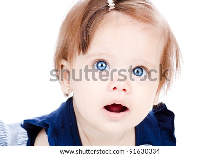 A closeup of a beautiful baby girl looking towards the viewer, with her stunning blue eyes, isolated on white.