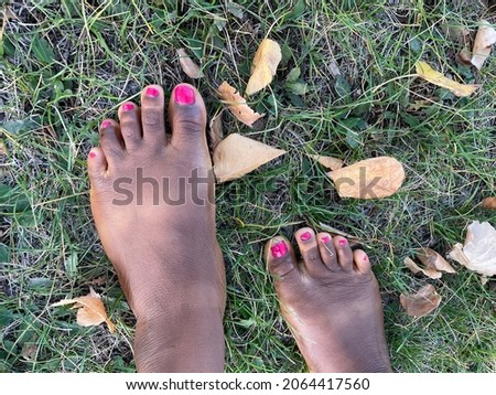 A closeup of a Black person's barefeet with grass and leaves underneath