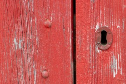 A closeup of a bright red vintage metal keyholder in a textured red wooden door. The exterior of the old woodshed has worn and wear patterns with some scuff marks.