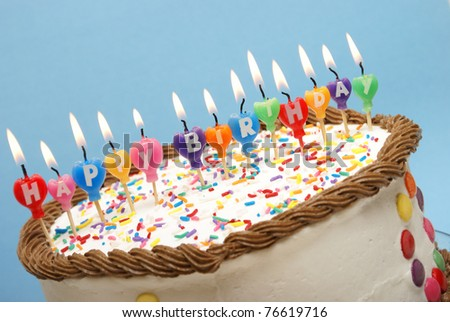 A closeup of a cake and it's candles that read happy birthday.