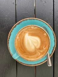 A closeup of a cappuccino cup on a rustic table