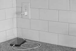 a closeup of a cell phone plugged in to a white subway tile wall outlet charging on a granite countertop, black and white 45 degree angle horizontal shot