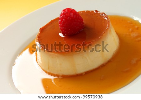 A closeup of a creme caramel with a yellow background.