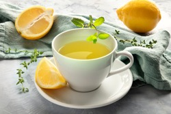 A closeup of a cup of green tea with lemons and herbs