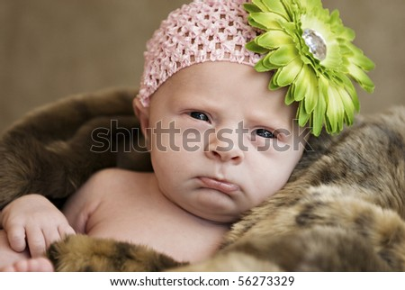A closeup of a cute frowning baby girl wearing hat with flower, selective focus with shallow depth of field