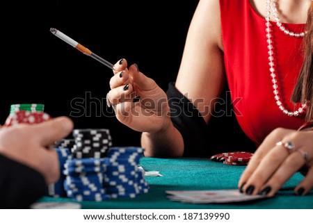 A closeup of a female casino gambles smoking a cigarette