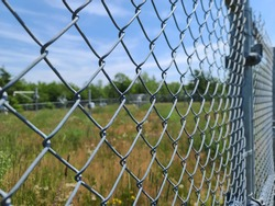 A closeup of a fence that is protecting a property. The metal gate is a chain link fence with barbed wire at the very top of it.