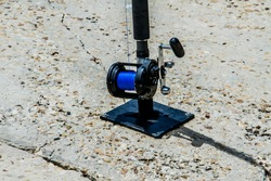 A closeup of a fishing rod with blue reel resting on a rod hole on a concrete surface