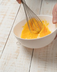 A closeup of a hand beating an egg on a bowl with an egg beater on a white plank table