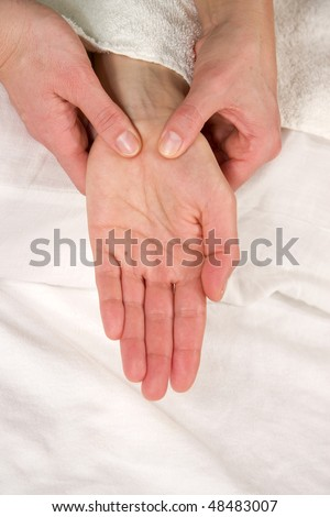 a closeup of a hand of a mature natural woman having a hand reflex zone massage at the thenar
