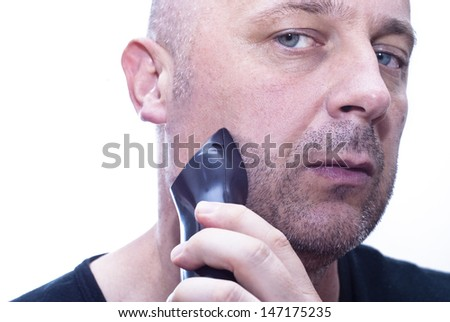 A closeup of a  man shaving his beard off with an electric shaver.