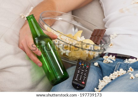 A closeup of a man with a bowl of junk food, beer and a remote control