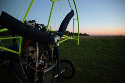 A closeup of a motorized paraglider trolley with a non-revolving engine and a sheathed propeller on an airfield in the late evening. Extreme sports. Paragliding and small aircraft.