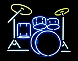 A closeup of a neon drum set sign on display in a business window