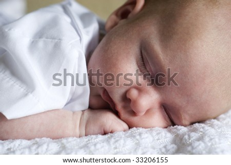 A closeup of a newborn baby boy sleeping, full frame with selective focus, horizontal
