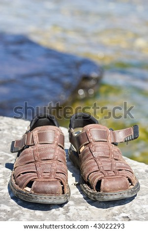 A closeup of a pair of brown sandals on a rocky ledge, with an expanse of water behind.