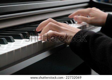 A closeup of a pair of hands as they press on piano keys.