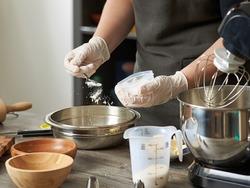 A closeup of a pastry chef adding flour or baking powder to a mixer bowl to make a dessert dough.