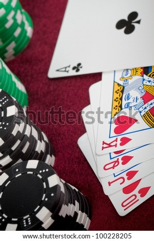 A closeup of a poker hand that just misses getting a Royal Flush. There is straight of hearts-ten, Jack, Queen, King but the Ace is a club with checkered poker chips lined up on the left.