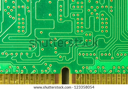 A closeup of a printed circuit board with gold contacts