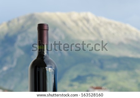 A closeup of a red wine bottle neck in front of a mountain