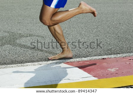 A closeup of a runners feet while barefoot running on a track