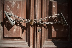 A closeup of a rusty chain with a lock on an old wooden door under the sunlight