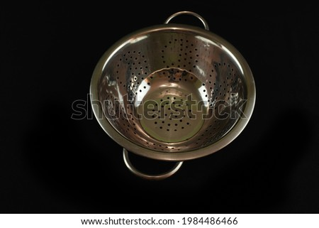 A closeup of a strainer on a black background Stock photo ©