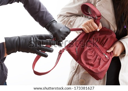 A closeup of a thief wearing gloves holding a woman's bag