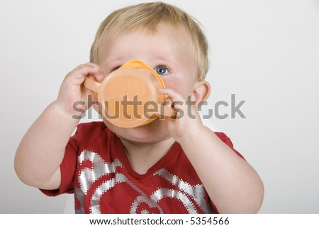 A closeup of a toddler drinking from a cup