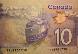A closeup of a train in the Rocky Mountains on the back of a Canadian 10 dollar polymer bill.