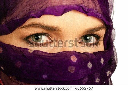 A closeup of a very beautiful Indian or Asian woman wearing a purple veil. Isolated over white