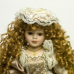 a closeup of a vintage Doll with beautiful golden tresses on a white background