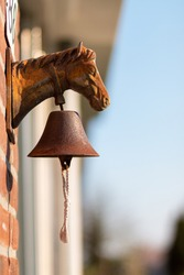 A closeup of a vintage horse head doorbell with an old rusted bell