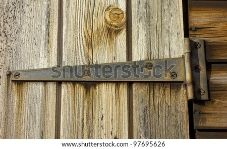 A closeup of a weathered shed door hinge.