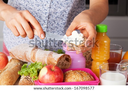 A closeup of a woman making lunch for her kids