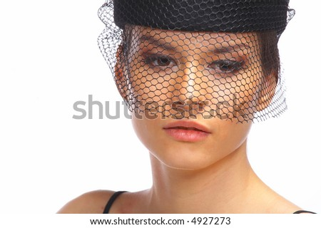 A closeup of a woman's face in black and white. She is wearing a vintage hat with a net