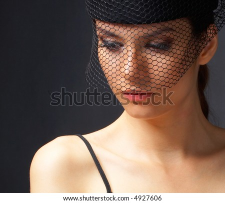 A closeup of a woman\'s face in black and white. She is wearing a vintage hat with a net
