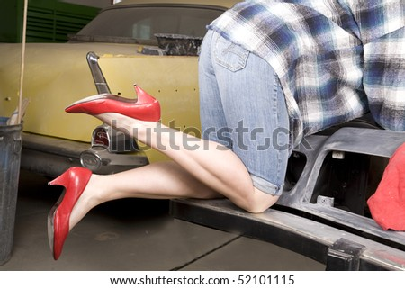 A closeup of a woman wearing her red high heels working on restoring a car.