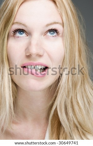 A closeup of a woman with a wishful expression biting her lip.