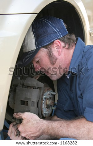 A closeup of an auto mechanic concentrating as he fixes a car.