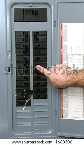 A closeup of an electrical panel with an electrician turning off the breaker so he can work safely according to OSHA standards.