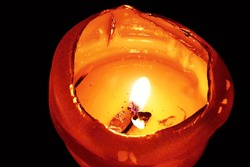A closeup of an illuminated orange burning candle in dark.