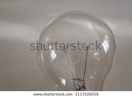 A closeup of an incandescent light bulb with a broken filament and window reflections on the glass surface