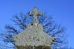 A closeup of an old stone cross in a cemetery in France against a bare tree and blue sky background