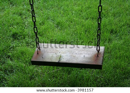 A closeup of an old wooden swing sitting above lush green grass.