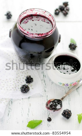 A closeup of blackberry jam on a white wooden table