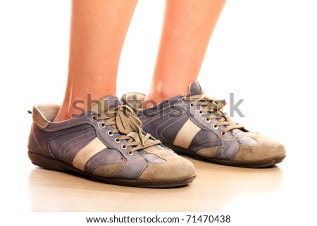 A closeup of female legs trying on too big male shoes over white background