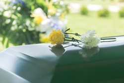 A closeup of flowers atop a funeral casket outdoors.