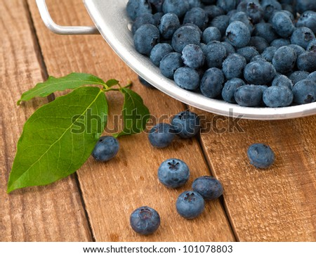 A Closeup of Freshly Picked and Wet Blueberries in a Colander on Weathered Wood Boards for a Vintage Look